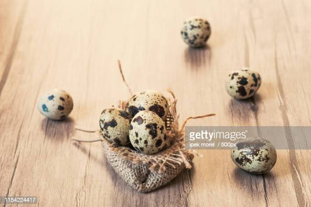 quail eggs on brown wooden background easter concept - ipek morel stock pictures, royalty-free photos & images