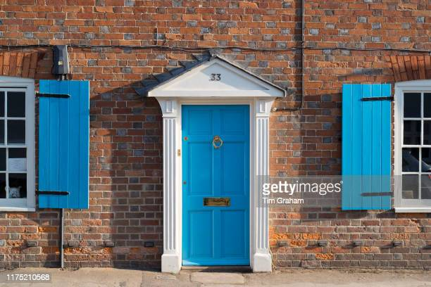 Quaint door and windows painted bright blue of brick built English cottage with portico and shutters in Ramsbury, Wiltshire, United Kingdom.