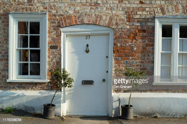 Quaint door and windows painted white of brick built typical English cottage with bay trees in Ramsbury, Wiltshire, United Kingdom.