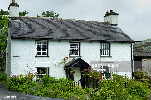 Quaint lakeland cottage and country lane at Troutbeck in the Lake District National Park Cumbria UK