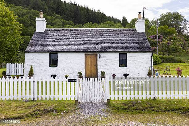 Quaint traditional highland stone bungalow cottage with white paling fence at Appin Argyllshire in the Highlands of Scotland