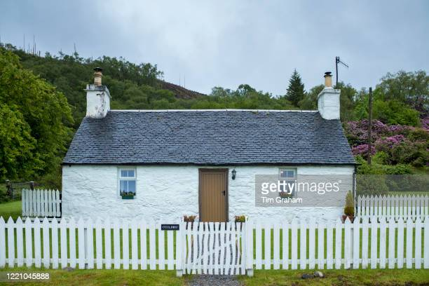 "Quaint traditional whitewashed cottage with white paling fence and tiled roof in Appin, Argyll and Bute, Scotland""n."