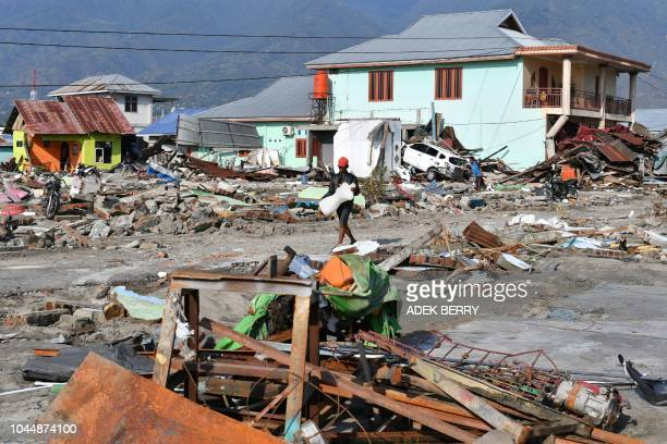 A quake survivor carries away a salvaged mannequin past debris of houses in Lere subdistrict in Palu Indonesia's Central Sulawesi on October 3 after...