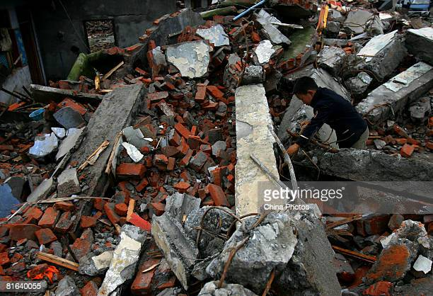 Quake survivor salvages what he can from the debris of destroyed buildings at the Yinghua Township on June 19, 2008 in Shifang of Sichuan Province,...