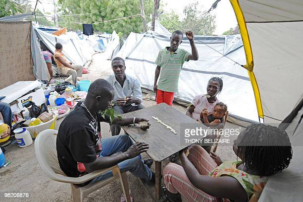 Quake victims play a game of dominoes on April 01 2010 in a tent city of PetionVille a neighborhood of PortauPrince The global community has pledged...