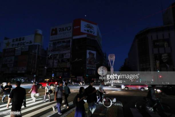 Quakeaffected residents walk as an electrical blackout shrouds the shopping district in Sapporo on September 6 after an earthquake hit the northern...