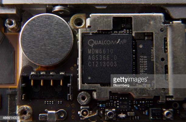 A Qualcomm Inc baseband processor sits inside a smartphone sold as an Apple Inc iPhone 4S in an arranged photograph in Hong Kong China on Saturday...
