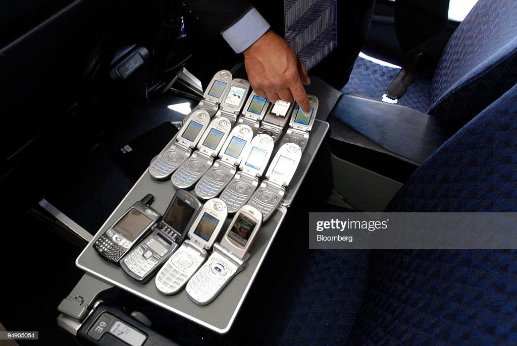 A Qualcomm, Inc , employee monitors a batch of cell phones