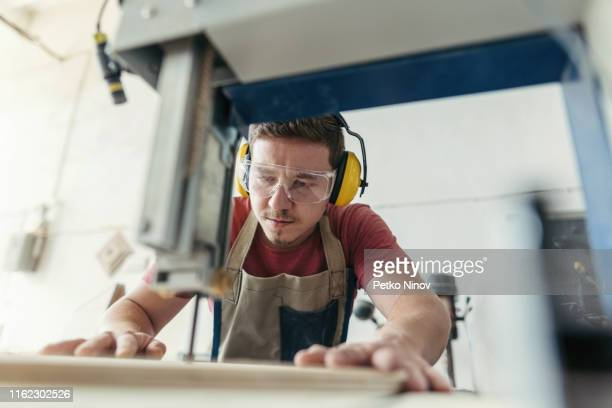 qualified carpenter working on grinding machine - carpenter stock pictures, royalty-free photos & images