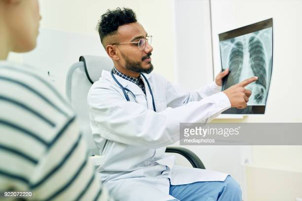 qualified doctor showing x-ray image of lungs to patient - outpatient care stock pictures, royalty-free photos & images