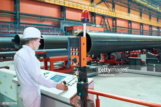 qualified factory employee setting up machine - metal industry stock pictures, royalty-free photos & images