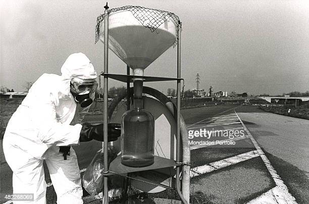 A qualified worker wearing white coverall and a gas mask appointed to free from pollution the A area in Seveso analyzes a sample survey of liquid on...