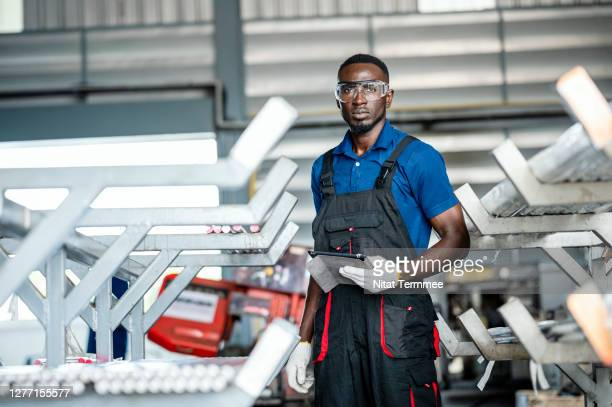 quality control engineer wearing bib overalls standing in material steel pipe storage shelf for production. quality control management. - making stock pictures, royalty-free photos & images