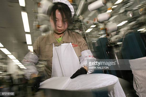 A quality control inspector at the Langsha Socks company checks for blemishes at their factory in the city of Yiwu Zhejiang Province 29 March 2006...