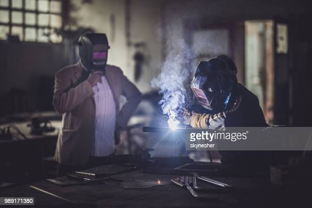 Qualitätskontrolle-Inspektor Überwachung Metall Schweißen in einer Werkstatt.
