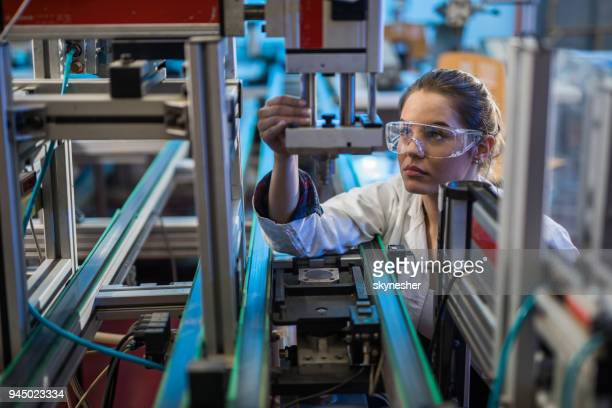Quality control worker analyzing machine part in laboratory.