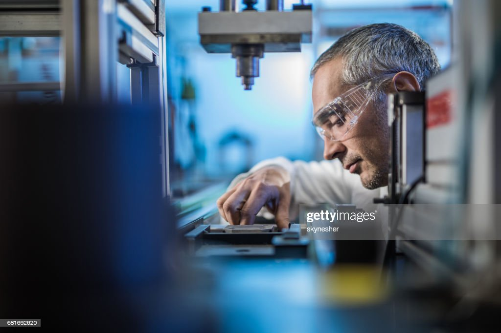 Quality control worker analyzing scientific experiment on a manufacturing machine. : Stock Photo
