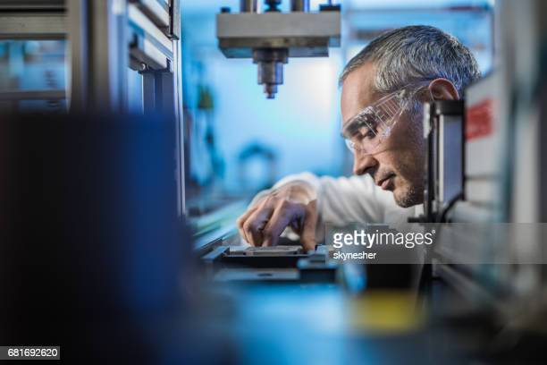 quality control worker analyzing scientific experiment on a manufacturing machine. - novo imagens e fotografias de stock