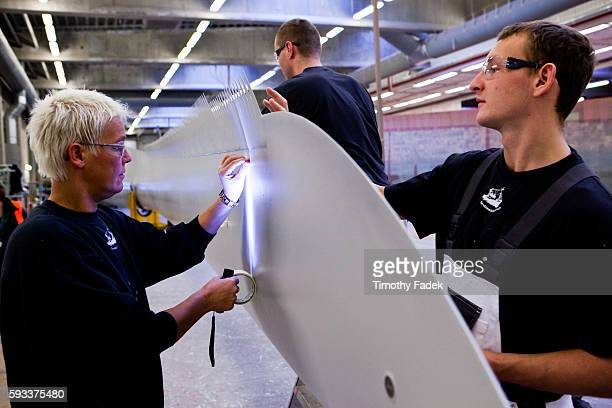 A quality control worker left inspects a nearfinished painted blade while workers mount an air stabilizer at the Siemens wind turbine blade plant in...