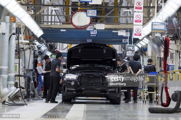 Quality control workers inspect a BMWX5 xDrive40e M Sport plugin hybrid vehicle at the BMW AG assembly plant in Amata Rayong province Thailand on...