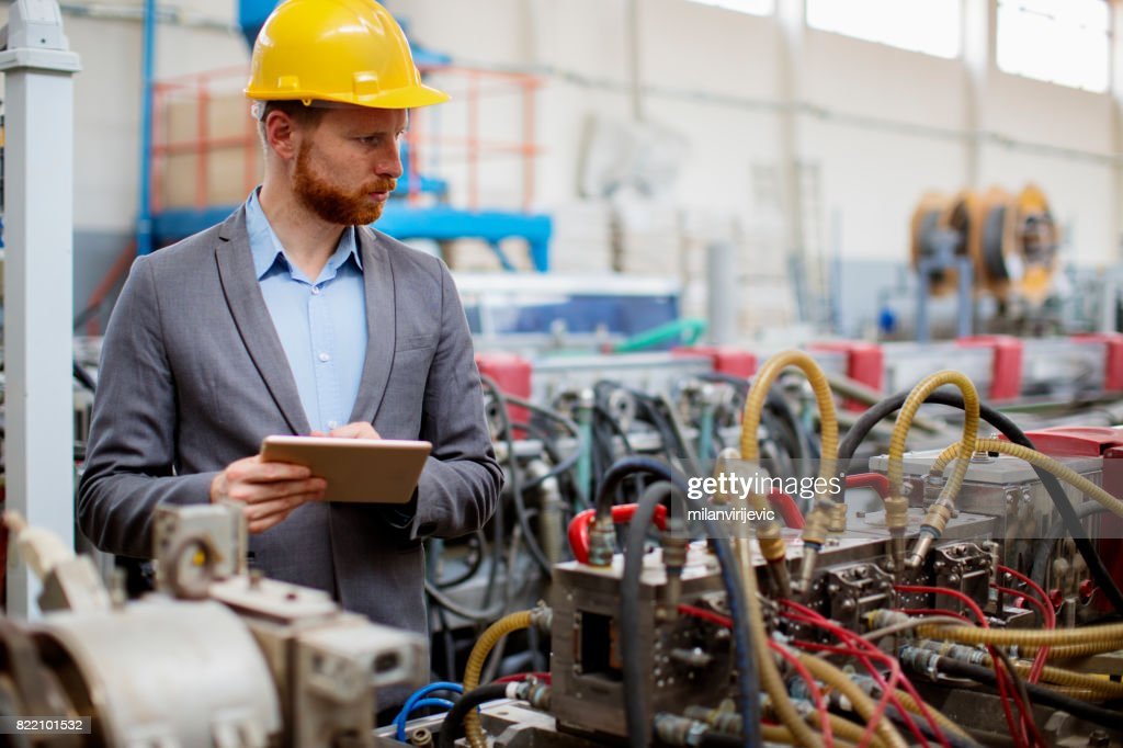 Quality controller checking machines in factory : Stock Photo