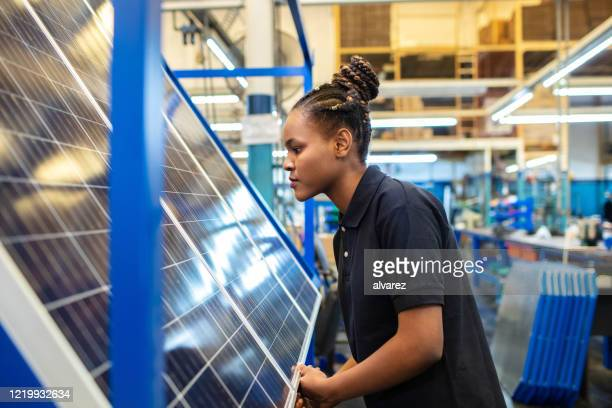 quality engineer examining solar panels in factory - gender identity stock pictures, royalty-free photos & images