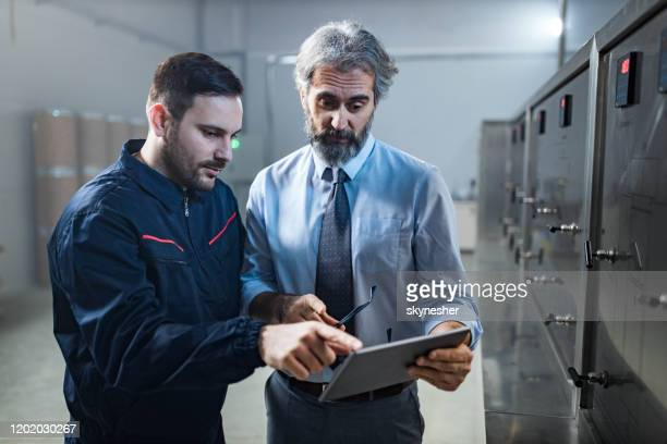 quality inspector and manual worker using digital tablet in a factory. - touchpad stock pictures, royalty-free photos & images