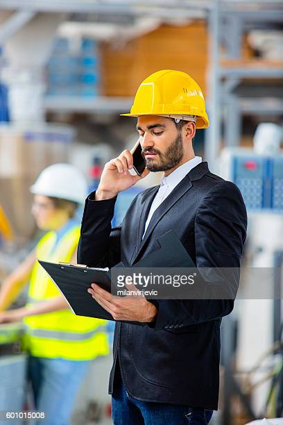 Quality inspector revising quality reports and using smartphone