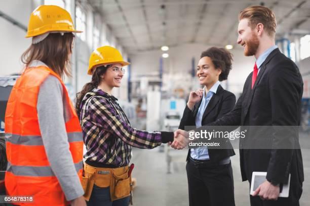 Kwaliteit inspecteurs schudden handen met workes in fabriek