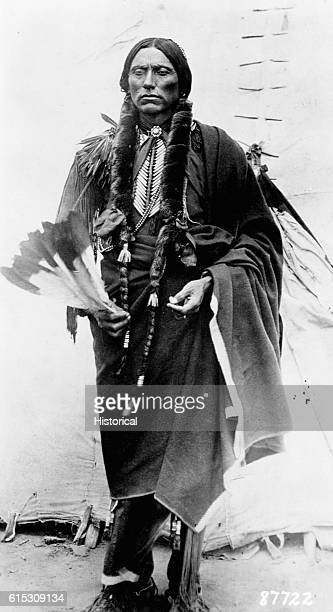 Quanah Parker a Kwahadi Comanche chief fulllength standing in front of tent | Location outdoors