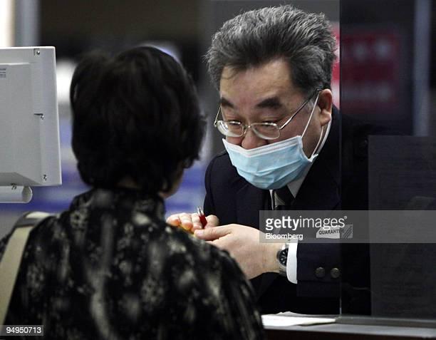 Quarantine officer wearing a surgical mask checks a passenger at Narita International Airport in Narita City, Chiba Prefecture, Japan, on Thursday,...