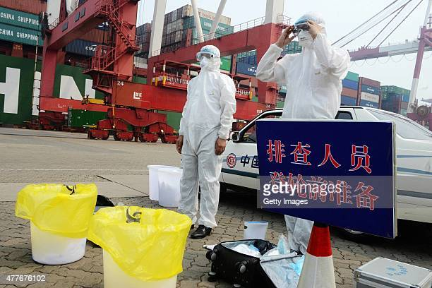 Quarantine officers prepare before boarding ship for inspection during antiMERS drill at Qingdao Port on June 18 2015 in Qingdao Shandong province of...