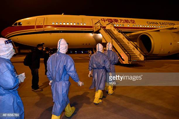 Quarantine officers walk to welcome back an 82member medical team sent to the Republic of Liberia to assist in the fight against Ebola at Chongqing...