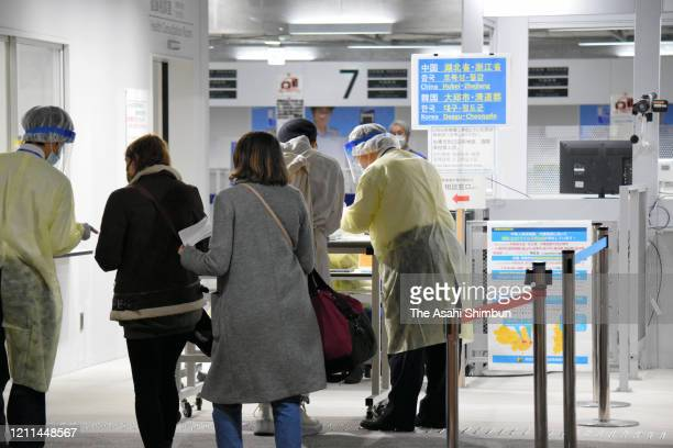 Quarantine officials in protective gear ask each passenger arriving on a flight from Seoul to fill in a questionnaire at the quarantine counter of...