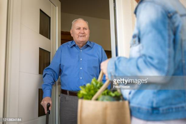 quarantine – woman helping senior man - assistance stock pictures, royalty-free photos & images