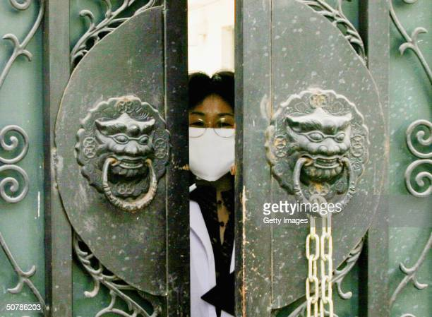 Quarantined medical worker, wearing a face mask to protect against the Severe Acute Respiratory Syndrome virus peeks out of the entrance gate of the...