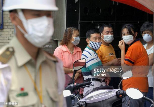 Quarantined residents chat as a masked military policeman stands guard over the sealed-off area of Huachang apartments in the Wanhua district of...