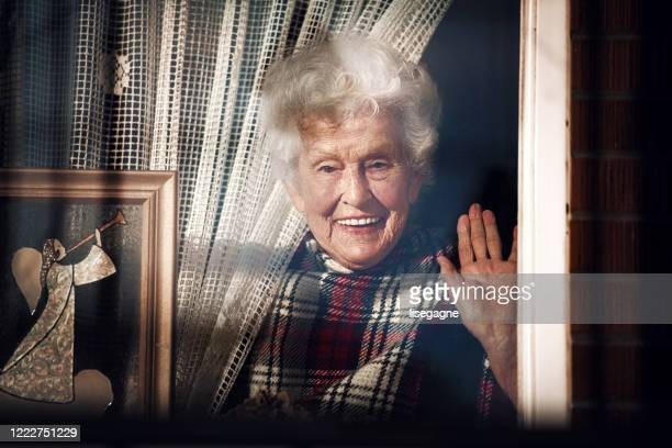 quarantined senior woman - photographed through window stock pictures, royalty-free photos & images
