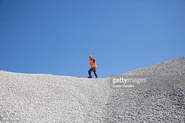 Quarry worker chatting on smartphone on top of quarry gravel mound