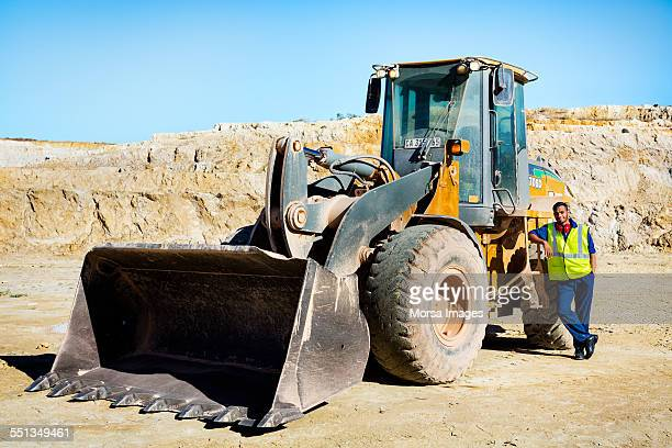 Quarry worker leaning on bulldozer at site