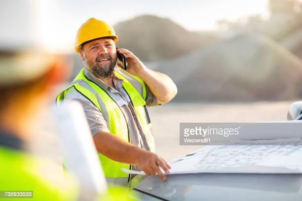 Quarry worker on site talking on the phone