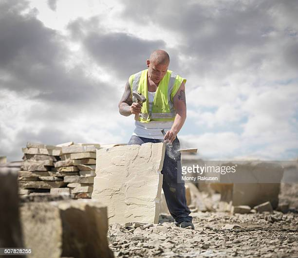 Quarry worker shaping sandstone in Yorkshire stone quarry