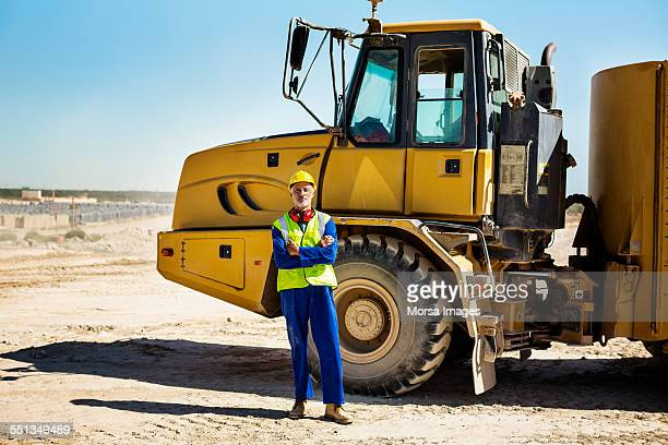 Quarry worker standing against bulldozer
