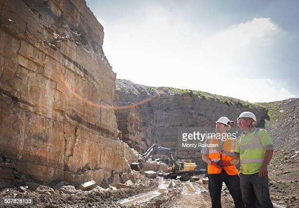 Quarry workers inspecting rock strata in stone quarry