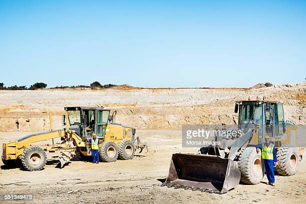 Quarry workers leaning on bulldozers
