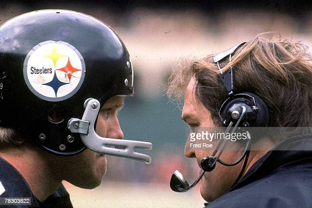 Quarteback Terry Bradshaw of the Pittsburgh Steelers confers with head coach Chuck Noll duing a game against the Cleveland Browns at Three Rives...