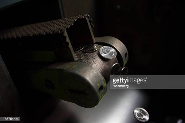 US quarter dollar coins move down a conveyor belt after being pressed at the US Mint in Philadelphia Pennsylvania US on Wednesday July 17 2013 Some...