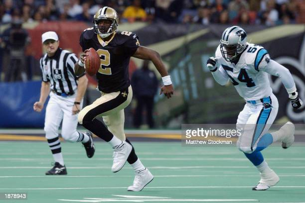 Quarterback Aaron Brooks of the New Orleans Saints is chased out of the pocket by linebacker Will Witherspoon of the Carolina Panthers during the NFL...