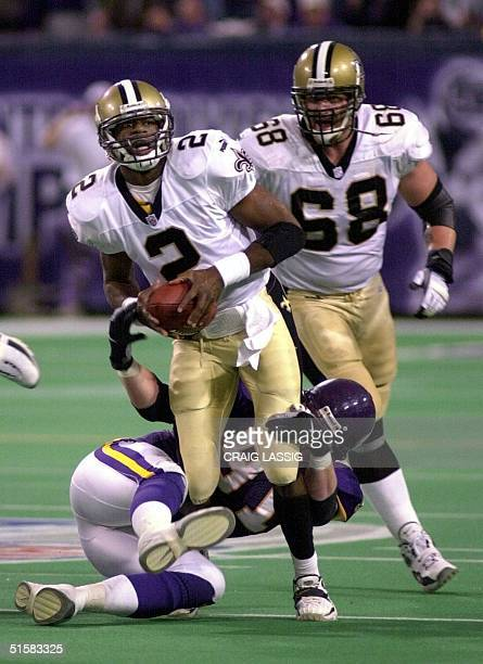 Quarterback Aaron Brooks of the New Orleans Saints is sacked by John Burroughs of the Minnesota Vikings as Saints lineman Kyle Turley looks on 06...