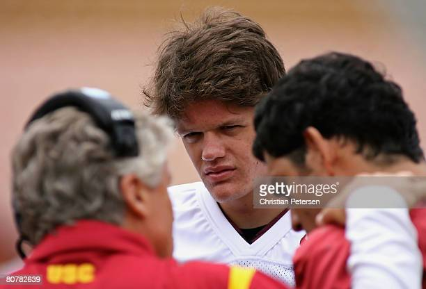 Quarterback Aaron Corp of the USC Trojans white team looks on as head coach Pete Carroll talks with Mark Sanchez during the spring practice game at...